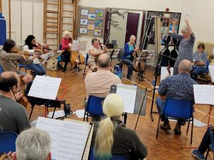 Conductor Fiona Crawley rehearsing with the Royal Forest of Dean Orchestra and Liz Lane